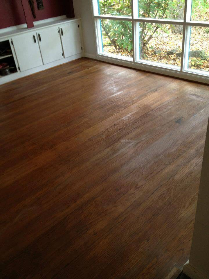 A damaged and beat up hardwood floor in a living room